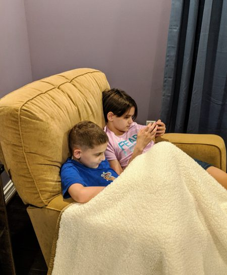 Kids sharing chair while using phones