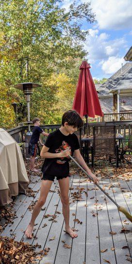 Kids sweeping leaves on deck