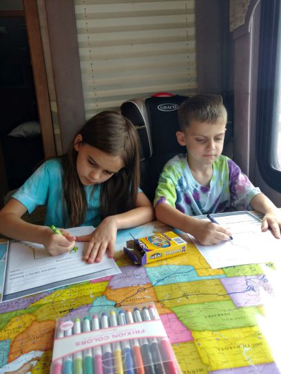 Kids coloring at table with map on it